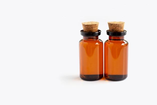 Bouteille brune aux huiles essentielles sur blanc
