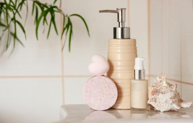 Bouteille en céramique de bain, savon, coquille et bombe de bain sur fond intérieur de salle de bain floue avec lavabo