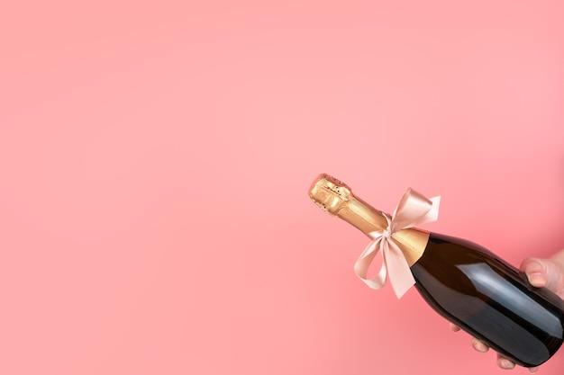 Une bouteille de champagne avec un arc sur fond rose