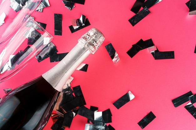 Bouteille de champagne avec de l'argent scintille à plat sur fond de papier rose