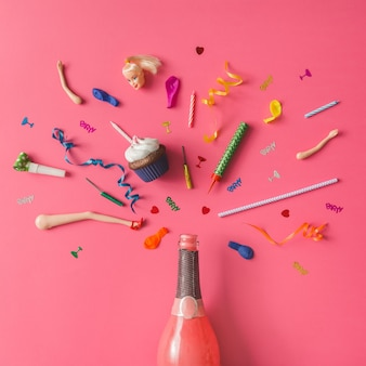 Bouteille de champagne avec des articles de fête colorés sur un mur rose. mise à plat.