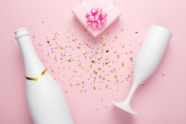 Bouteille de champagne blanc, boîte-cadeau et verre de champagne avec des confettis sur fond rose.