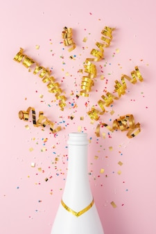 Bouteille de champagne blanc avec des confettis et des banderoles de fête sur fond rose.