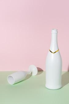 Bouteille de champagne blanc et verre de champagne sur une surface brillante.