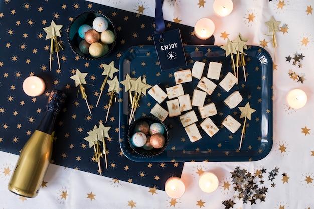 Bouteille de champagne avec des bonbons sur la table