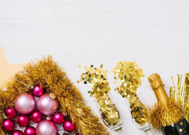 Bouteille de champagne avec des boules brillantes sur la table