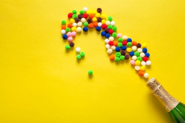 Bouteille de champagne avec des boules de coton colorées