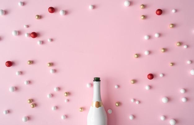 Bouteille de champagne avec des boules de décoration de paillettes rouges, or et blanches. carte de voeux de nouvel an parti fond rose avec espace copie. style minimal. composition à plat.