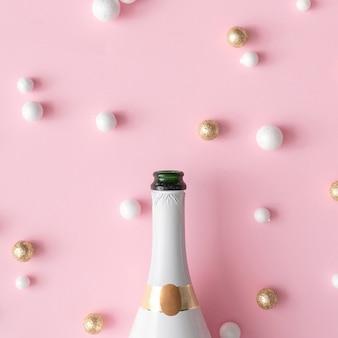 Bouteille de champagne avec des boules de décoration de paillettes rouges, or et blanches. carte de voeux de nouvel an parti fond rose. style minimal. composition à plat.