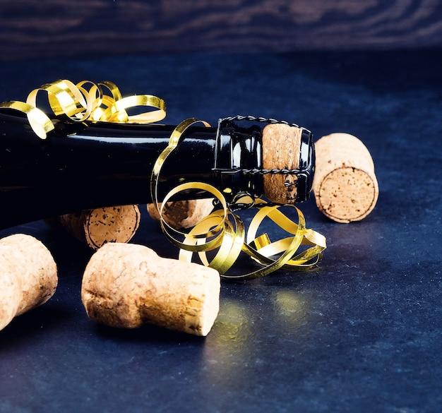 Bouteille de champagne et un certain nombre de tubes, concept de vacances, fond sombre