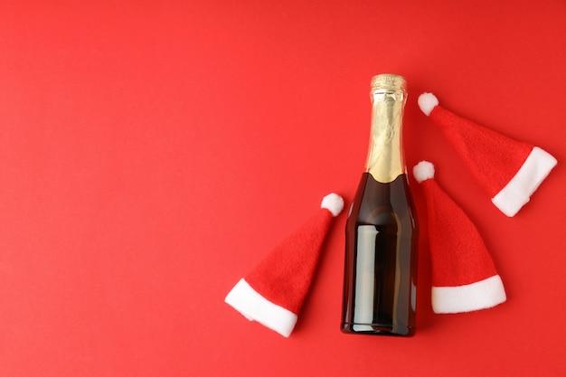 Bouteille de champagne et chapeaux de père noël sur fond rouge.