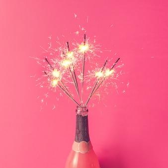 Bouteille de champagne avec des cierges magiques sur mur rose. mise à plat.