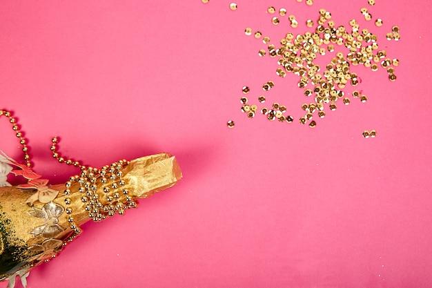 Bouteille de champagne avec des confettis dorés sur fond de papier rose.