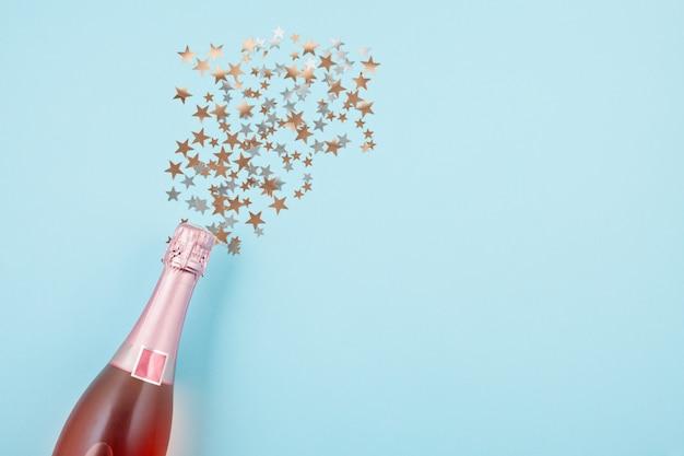 Bouteille de champagne avec des confettis sur fond bleu