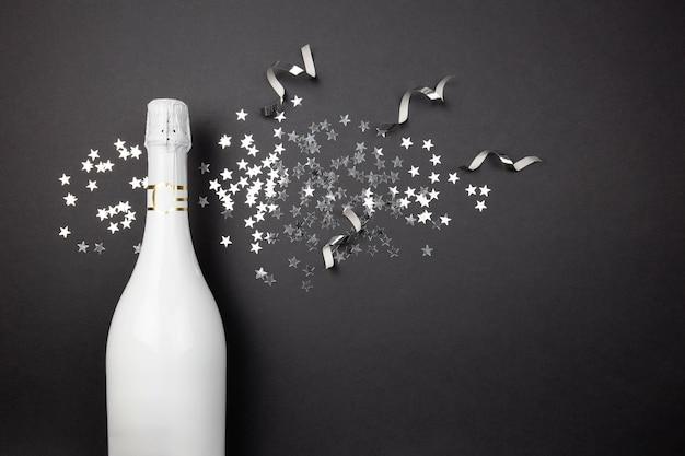 Bouteille de champagne et confettis sur fond sombre. mise à plat de la composition de la célébration.
