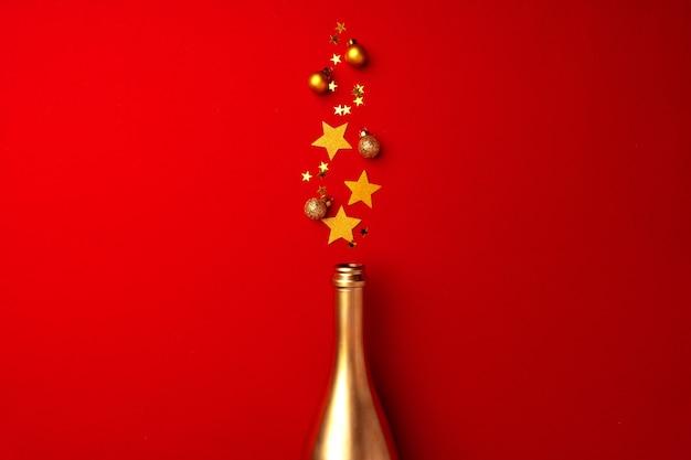 Bouteille de champagne avec des confettis mousseux sur plat rouge poser