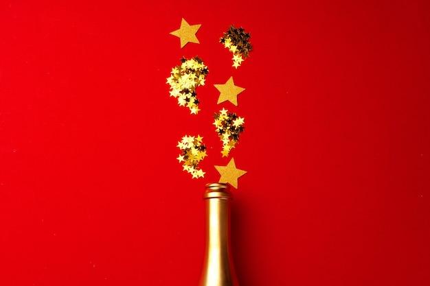 Bouteille de champagne avec des confettis mousseux sur rouge