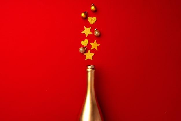 Bouteille de champagne avec des confettis mousseux sur la vue de dessus plat rouge