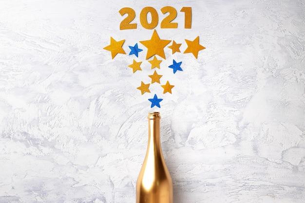 Bouteille de champagne avec des confettis à plat, vue du dessus