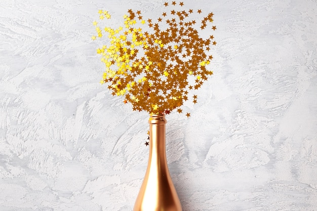 Bouteille de champagne avec des confettis à plat