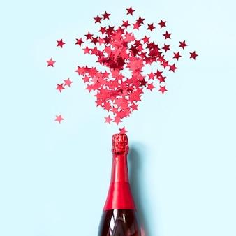 Bouteille de champagne et confettis rouges en forme d'étoiles sur bleu.