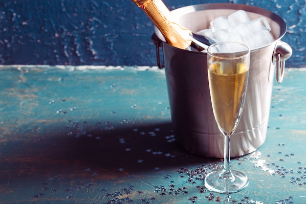 Bouteille de champagne dans un seau avec de la glace et des coupes de champagne