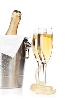 Bouteille de champagne dans un seau à glace, deux verres et décor de noël. isolé sur fond blanc