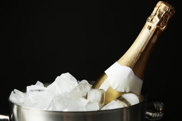 Bouteille de champagne dans un seau avec de la glace, sur fond noir