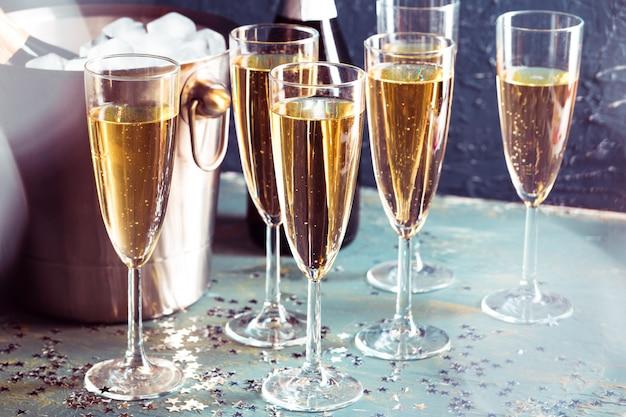 Bouteille de champagne dans seau avec glace et verres de champagne