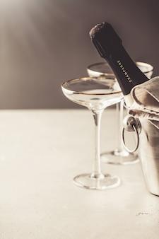 Bouteille de champagne dans un seau et des verres sur du béton