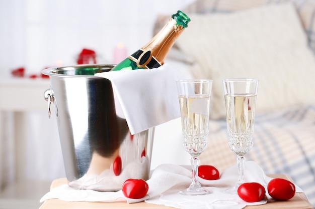 Bouteille de champagne dans un seau, des verres et des pétales de rose pour célébrer la saint-valentin