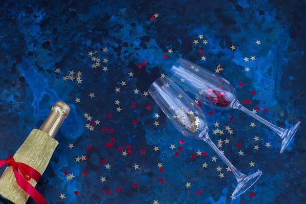 Bouteille de champagne, deux verres et confettis