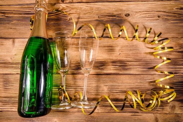 Bouteille de champagne et deux verres à vin décorés de ruban doré sur une table en bois rustique. vue de dessus