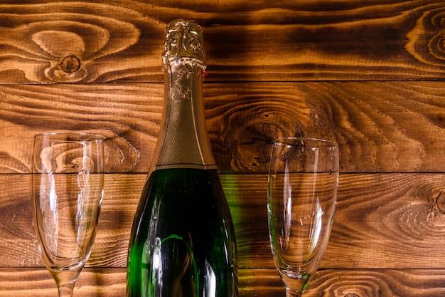 Bouteille de champagne et deux verres à vin sur une table en bois rustique. vue de dessus