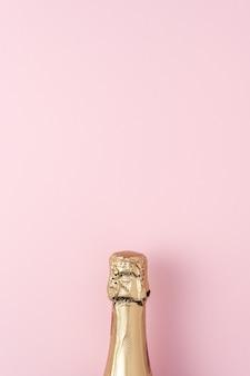 Bouteille de champagne doré sur fond rose.