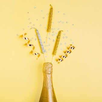 Bouteille de champagne doré vue de dessus et rubans avec des bougies