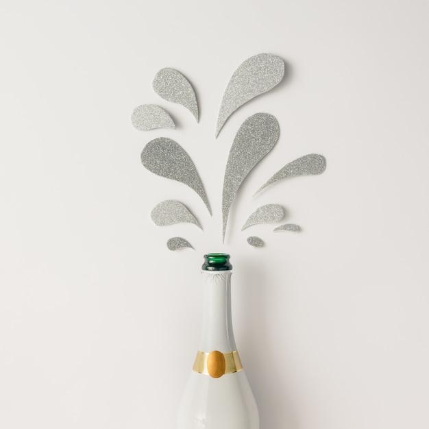 Bouteille de champagne avec des éclaboussures scintillantes d'argent sur une surface blanche