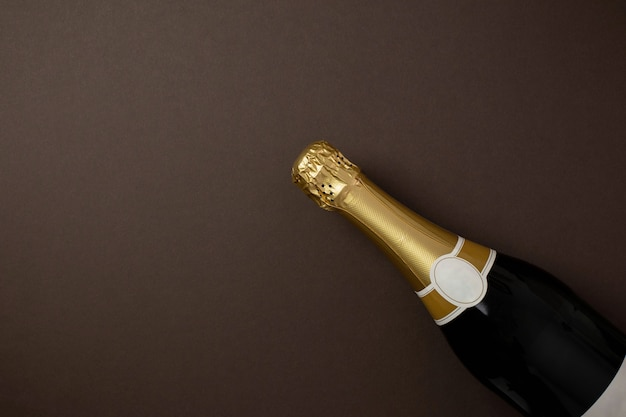 Bouteille de champagne avec étiquette dorée vierge sur fond marron foncé avec espace de copie.