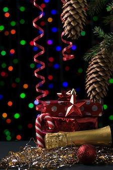 Une bouteille de champagne fermée et des cadeaux emballés sous un arbre de noël. concept de noël et nouvel an.