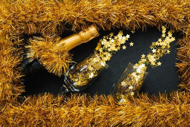 Bouteille de champagne avec des lunettes dans un cadre de guirlandes