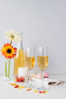 Bouteille de champagne avec des lunettes et des fleurs