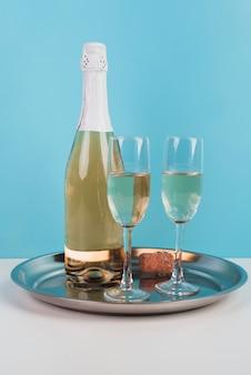 Bouteille de champagne avec des lunettes sur un plateau