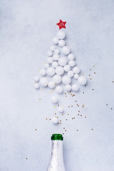 Bouteille de champagne de noël avec des paillettes de couleur blanche sur blanc.