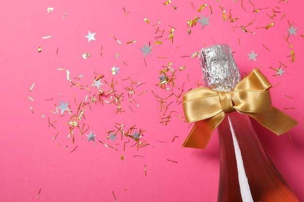 Bouteille de champagne avec noeud et paillettes sur rose, gros plan