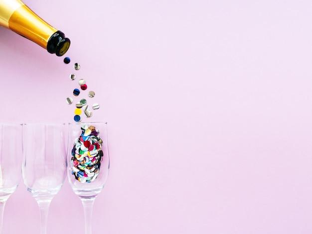 Bouteille de champagne or et verres avec des confettis