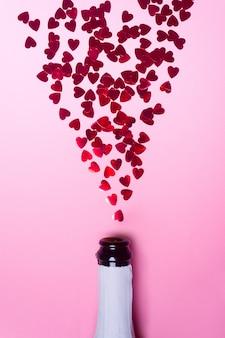 Bouteille de champagne avec des paillettes en forme de coeur sur rose.