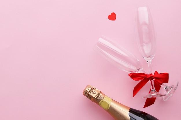 Une bouteille de champagne pour la saint valentin, une surface rose