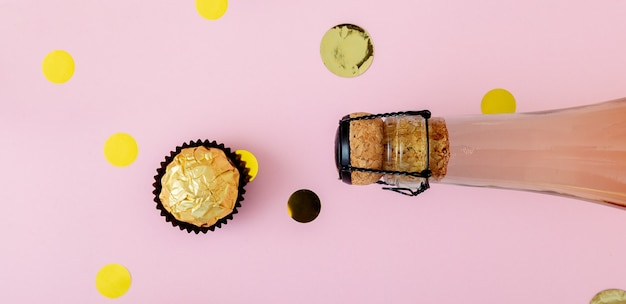 Bouteille de champagne rose avec des confettis, des bonbons dorés
