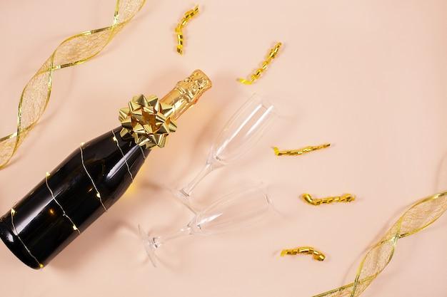 Bouteille de champagne avec des rubans dorés et des confettis. célébration du nouvel an