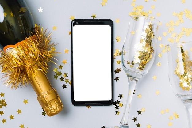 Bouteille de champagne avec smartphone sur table